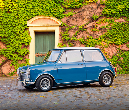 AUT 23 BK0042 01 © Kimball Stock 1970 Mini Cooper S Blue 3/4 Front View On Pavement By House