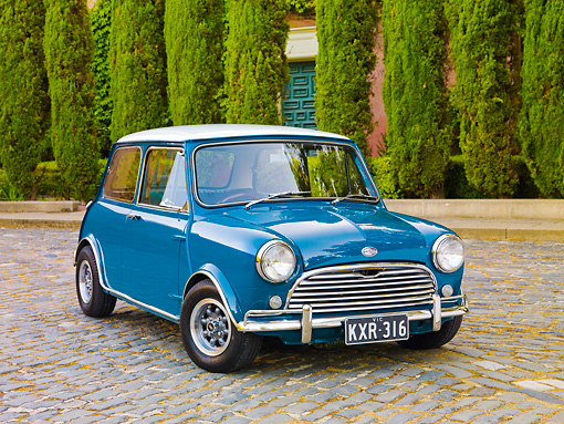 AUT 23 BK0046 01 © Kimball Stock 1970 Mini Cooper S Blue 3/4 Front View On Pavement By Shrubs