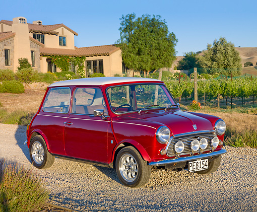 AUT 23 BK0048 01 © Kimball Stock 1975 Morris Mini 1000 Red 3/4 Front View On Gravel By House