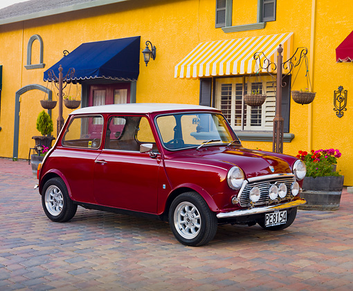 AUT 23 BK0050 01 © Kimball Stock 1975 Morris Mini 1000 Red 3/4 Front View On Brick Road By Yellow Building