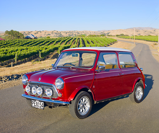 AUT 23 BK0055 01 © Kimball Stock 1975 Morris Mini 1000 Red 3/4 Front View On Road By Crops