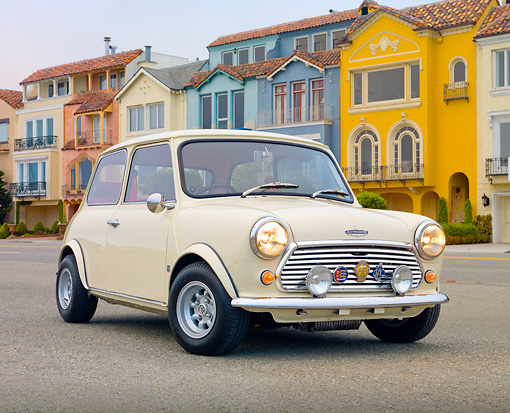 AUT 23 BK0064 01 © Kimball Stock 1971 Mini 1000 Cream 3/4 Front View On Pavement By Colorful Houses
