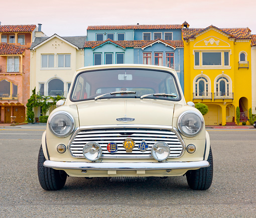 AUT 23 BK0065 01 © Kimball Stock 1971 Mini 1000 Cream Front View On Pavement By Colorful Houses