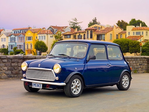 AUT 23 BK0066 01 © Kimball Stock 1971 Austin Mini Cooper Blue 3/4 Front View On Pavement By Colorful Houses
