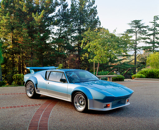 AUT 23 RK0265 05 © Kimball Stock 1971 De Tomaso Pantera Blue And Silver 3/4 Front View On Pavement By Trees Blue Sky