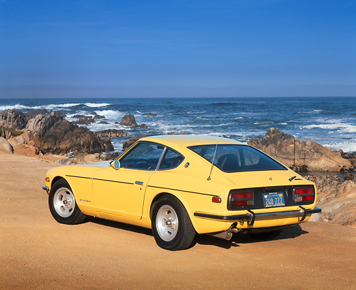 AUT 23 RK0367 04 © Kimball Stock 1971 Datsun 240Z Sport Yellow 3/4 Rear View On Sand By Ocean And Rocks