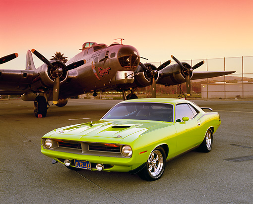 AUT 23 RK0459 02 © Kimball Stock 1970 Plymouth 'Cuda Lime Green 3/4 Front View On Pavement By Plane Red Sky