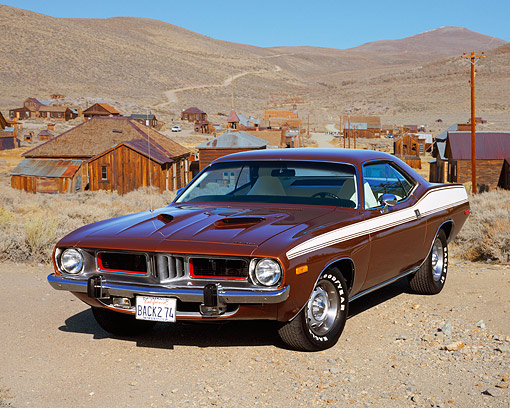 AUT 23 RK0471 03 © Kimball Stock 1974 Plymouth Cuda Sienna Burgundy Front 3/4 View On Pavement By Grass Blue Sky