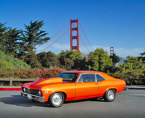 AUT 23 RK0514 02 © Kimball Stock 1972 Chevrolet Nova Street Rod Orange 3/4 Side View On Pavement By SF Bridge And Bushes