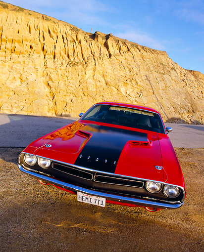 AUT 23 RK0527 02 © Kimball Stock 1971 Dodge Challenger 426 Hemi Red And Black Slanted Head On On Sand By Rock