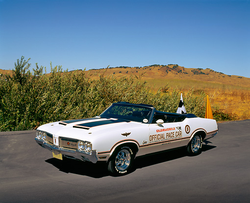 AUT 23 RK0638 05 © Kimball Stock 1970 Oldsmobile Cutlass Supreme Convertible Pace Car White Black Stripe 3/4 Front View On Pavement By Bushes