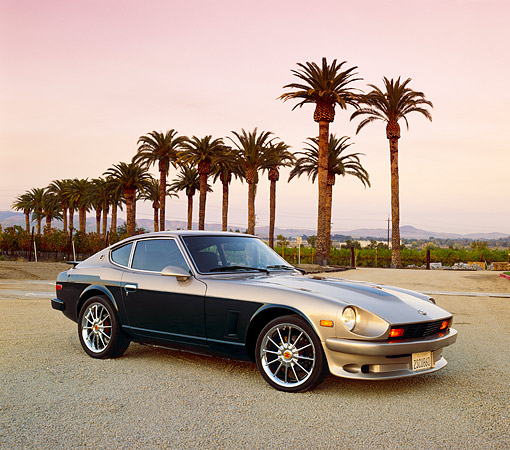 AUT 23 RK0697 04 © Kimball Stock 1976 Datsun 280Z Green And Gold 3/4 Side View On Gravel By Palm Trees Filtered