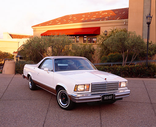 AUT 23 RK0729 03 © Kimball Stock 1978 Chevy SS El Camino White And Gold 3/4 Front View On Pavement By Trees And Building