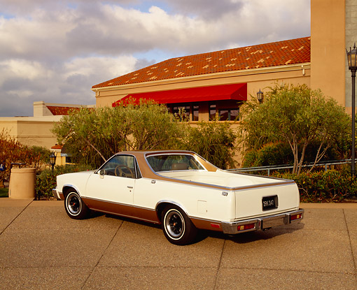 AUT 23 RK0732 04 © Kimball Stock 1978 Chevy SS El Camino White And Gold 3/4 Rear View On Pavement By Trees And Building