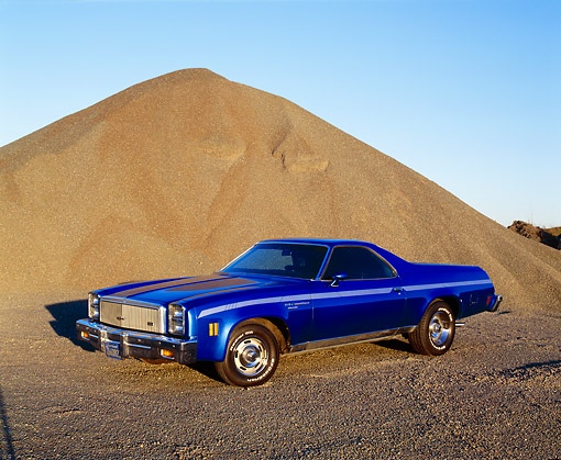 AUT 23 RK0733 03 © Kimball Stock 1977 Chevy El Camino Blue  Front 3/4 View By Pile Of Sand Blue Sky