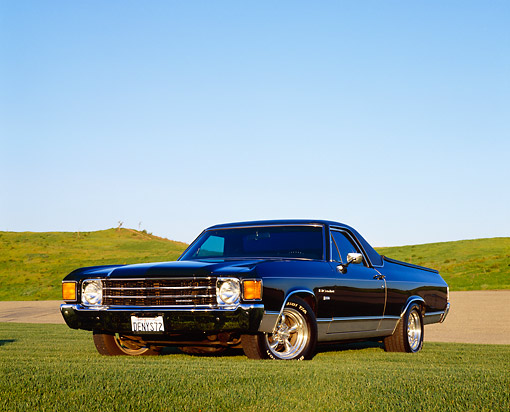AUT 23 RK0738 03 © Kimball Stock 1972 Chevy El Camino Black Low 3/4 Front View On Grass Blue Sky