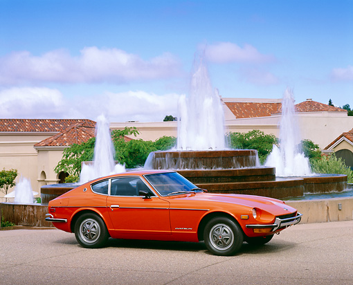 AUT 23 RK0770 05 © Kimball Stock 1972 Datsun 240Z Orange 3/4 Side View On Pavement By Water Fountain