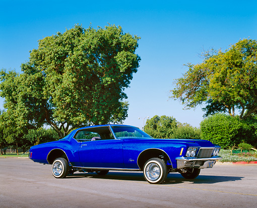 AUT 23 RK0773 04 © Kimball Stock 1971 Buick Riviera Lowrider Blue 3/4 Front View On Pavement By Trees