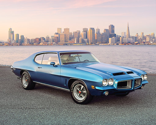 AUT 23 RK0844 04 © Kimball Stock 1972 Pontiac GTO 455 Blue 3/4 Side View On Pavement By Bay And City At Desk