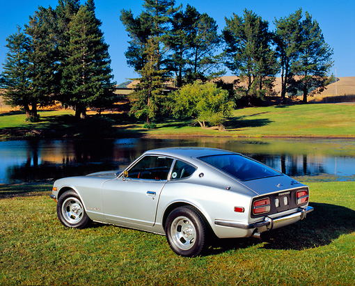 AUT 23 RK0863 01 © Kimball Stock 1971 Datsun 240Z Silver 3/4 Rear View On Grass By Water And Trees