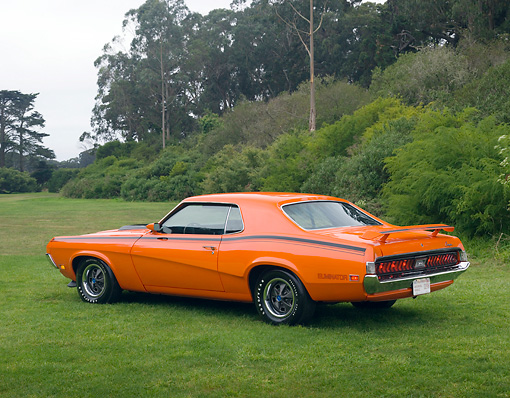 AUT 23 RK1124 01 © Kimball Stock 1970 Mercury Cougar Eliminator Orange 3/4 Rear View On Grass Trees Background