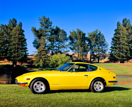 AUT 23 RK1639 01 © Kimball Stock 1971 Datsun 240Z Yellow 3/4 Front View On Grass By Trees
