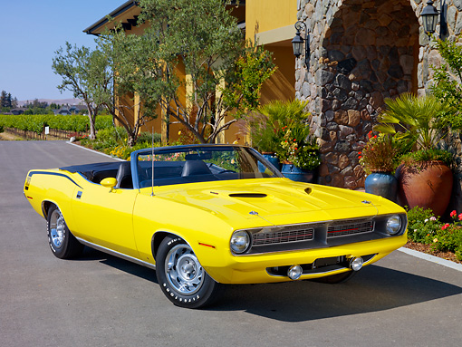 AUT 23 RK1854 01 © Kimball Stock 1970 Plymouth Barracuda 383 Convertible Yellow 3/4 Front View On Pavement By Building