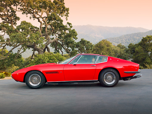 AUT 23 RK1898 01 © Kimball Stock 1971 Maserati Ghibli SS Red Profile View On Pavement By Trees And Hills