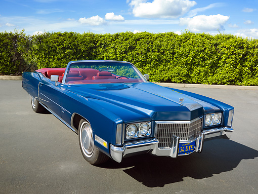AUT 23 RK1964 01 © Kimball Stock 1971 Cadillac El Dorado Convertible Blue 3/4 Front View On Pavement By Shrubs