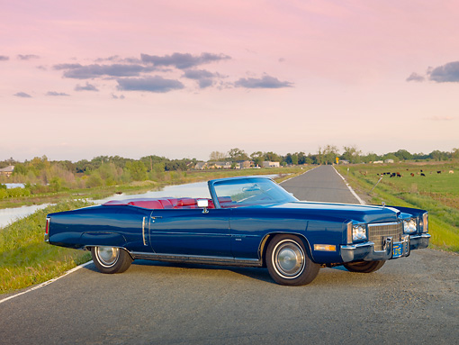 AUT 23 RK1966 01 © Kimball Stock 1971 Cadillac El Dorado Convertible Blue 3/4 Side View On Road By Marsh And Cows
