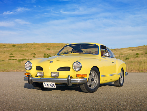 AUT 23 RK1989 01 © Kimball Stock 1973 VW Karmann Ghia Coupe Yellow 3/4 Front View On Pavement By Grassy Hill