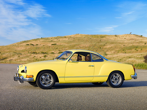 AUT 23 RK1990 01 © Kimball Stock 1973 VW Karmann Ghia Coupe Yellow 3/4 Side View On Pavement By Grassy Hill
