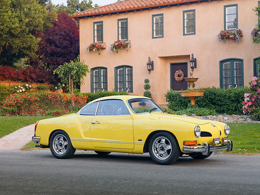 AUT 23 RK1992 01 © Kimball Stock 1973 VW Karmann Ghia Coupe Yellow 3/4 Front View On Pavement By House
