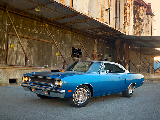 AUT 23 RK2012 01 © Kimball Stock 1970 Plymouth Road Runner Hemi Blue With Black Stripe 3/4 Front View On Pavement By Old Factory Building