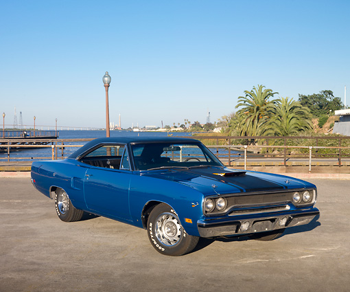 AUT 23 RK2014 01 © Kimball Stock 1970 Plymouth Road Runner Hemi Blue With Black Stripe 3/4 Front View On Pavement By Water And Palm Trees