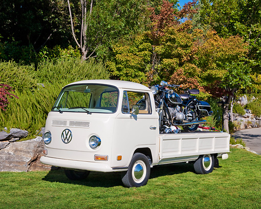 AUT 23 RK2035 01 © Kimball Stock 1970 VW Single Cab White With 1966 BMW R60/2 Motorcycle Black 3/4 Front View On Grass By Trees
