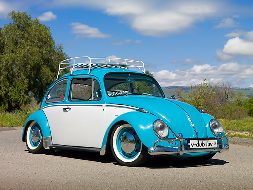 AUT 23 RK2079 01 © Kimball Stock 1970 VW Beetle Sedan Turquoise And White 3/4 Front View On Pavement By Grass And Trees