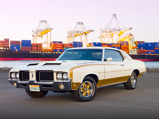 AUT 23 RK2080 01 © Kimball Stock 1972 Hurst Oldsmobile Cutlass White And Gold 3/4 Front View On Pavement By Shipping Yard