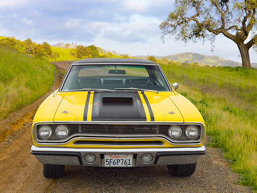 AUT 23 RK2155 01 © Kimball Stock 1970 Plymouth Road Runner 440 Six Pac Yellow With Black Stripe Front View On Dirt Road In Grassy Hills