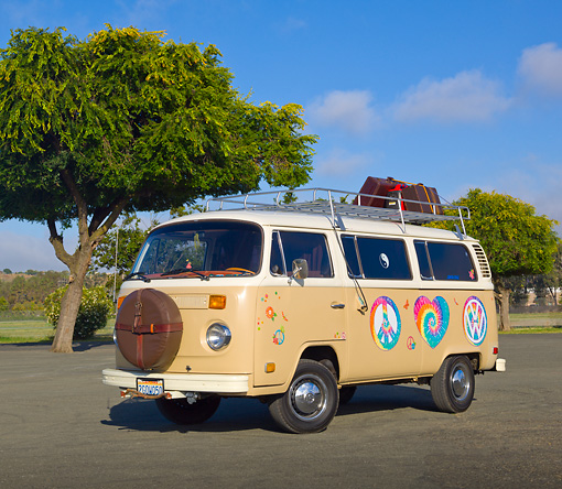 AUT 23 RK2158 01 © Kimball Stock 1974 Volkswagen Type 2 Tan With Hippie Logos 3/4 Front View On Pavement By Trees