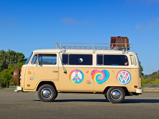 AUT 23 RK2160 01 © Kimball Stock 1974 Volkswagen Type 2 Tan With Hippie Logos Profile View On Pavement By Trees