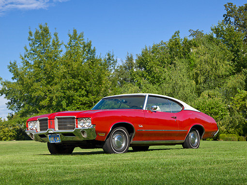 AUT 23 RK2163 01 © Kimball Stock 1971 Oldsmobile Cutlass S Red With White Roof 3/4 Front View On Grass By Trees