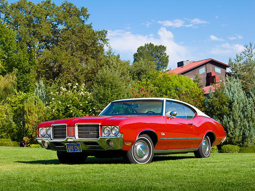 AUT 23 RK2164 01 © Kimball Stock 1971 Oldsmobile Cutlass S Red With White Roof 3/4 Front View On Grass By Trees