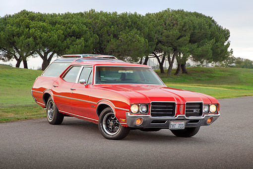 AUT 23 RK2166 01 © Kimball Stock 1971 Oldsmobile Vista Cruiser Red 3/4 Front View On Road By Trees