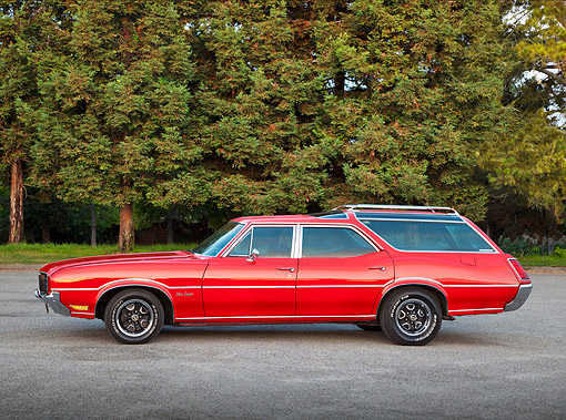 AUT 23 RK2169 01 © Kimball Stock 1971 Oldsmobile Vista Cruiser Red Profile View On Gravel By Trees