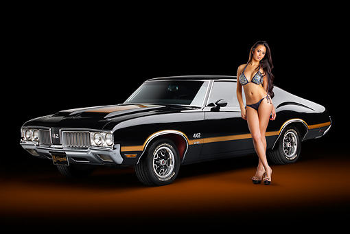 AUT 23 RK2189 01 © Kimball Stock 1970 Oldsmobile 442 W-30 Black With Gold Stripes 3/4 Front View In Studio With Swimsuit Model