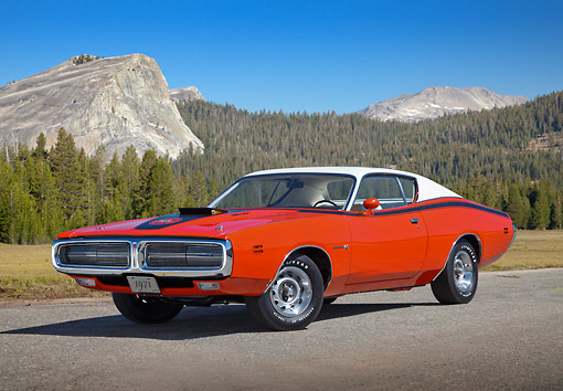 AUT 23 RK3425 01 © Kimball Stock 1971 Dodge Hemi Charger Orange With White Top 3/4 Front View On Pavement By Evergreen Trees And Mountains
