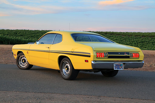 AUT 23 RK3429 01 © Kimball Stock 1971 Dodge Demon Yellow With Black Stripes 3/4 Rear View On Pavement By Vineyard At Dusk