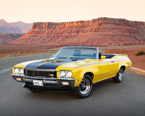 AUT 23 RK3450 01 © Kimball Stock 1971 Buick GSX Convertible Yellow 3/4 Front View On Road In Desert