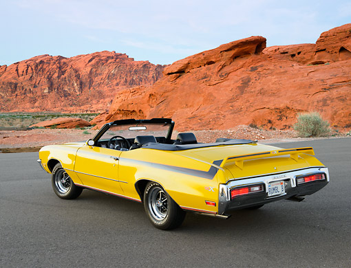 AUT 23 RK3454 01 © Kimball Stock 1971 Buick GSX Convertible Yellow 3/4 Rear View On Road In Desert